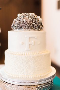 A glam two-tier wedding cake with a rhinestone topper! Add your newlywed initials in the icing for a personal accent. {@KeepsakeMP}