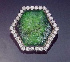 This important 17th Century carved emerald and diamond brooch is a lovely example of the Mogul style of gem engraving. The emerald weighs approximately 126 carats.