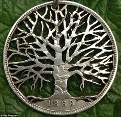 a coin carved into an intricate tree of life design
