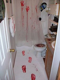 Cheap white rug, pint of red paint, dollar store towel, old shower curtain, gloves, mask, wig head, and coathanger.