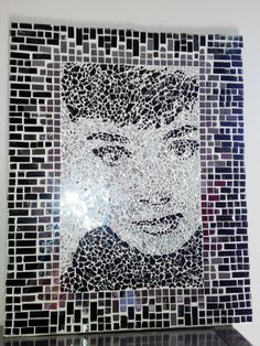 Pannello Audrey Hepburn con interno in mosaico craklé e contorno in tessere di vetro, nei colori del nero e argento/specchio. Panel Audrey Hepburn with internal mosaic crackle and contour glass tiles, in the colors of black and silver/mirror