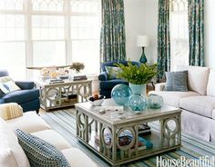 """A Seaside Living Room in Blue and Green  Designer Annie Selke said, """"Since this is a vacation house, I gave the family oversize tables on which they could do their puzzles and play games."""" Everly Square cocktail tables, Track Arm Sofas, and Bertram Chair by Annie Selke Home. Curtains are Shalini Bluemarine from Calico Corners. Featured in the"""