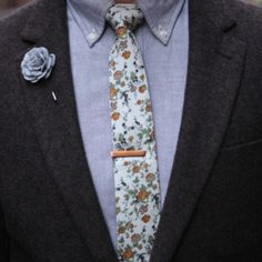 Floral print skinny tie, gold tie pin, blue-gray shirt, gray silk flower lapel pin, herringbone jacket.