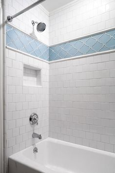This traditional white tile shower features a blue patterned accent trim near the large mounted shower head. The white tile extends from the ceiling to the white bathtub. A small indented cubby provides built-in storage for soap and other bath accessories.