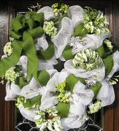"The wreath is 28"" in diameter, made with white basket weave deco mesh and adorned with a green burlap bow and ribbon in addition to a variety of white and green flowers"