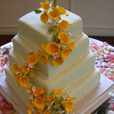 Calla lilies are hot this year for weddings and this soft, aqua, square wedding cake is accented with yellow callas make from sugar.