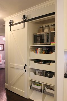 source: A Tree Lined Street   Fabulous pantry with sliding white barn door featuring iron hardware. The pantry features open shelving with room for cook books, glass canisters and a stainless steel microwave. Below the shelving the homeowners used stock components from Ikea to make pull-outs. Hardwood floors finish the kitchen design