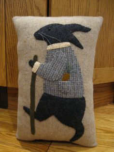 This whimsical pillow features a rabbit out for his afternoon stroll. Hes dressed in his best jacket and has his walking stick along as well. Ive done the rabbit in dark grey wool, his jacket in a wool plaid of blues with cream collar and cuff. He has a snack tucked into his pocket for when he gets hungry....a yummy carrot with the top done with a 3 dimensional effect. Stitched onto a woolen background. Luv the look of this guy! This pillow is hand stitched and measures 9 x 13 1/2. It is...