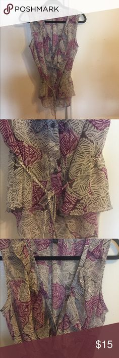 Banana Republic sleeveless blouse. Banana Republic sleeveless button up blouse. 100% polyester.  Cute ruffles and tie. Good condition. Some of the stitching in the back has been pulled as pictured. Banana Republic Tops Blouses