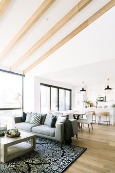open living spaces. great room ideas with vaulted ceilings. perfect hosting layout with the living room, dining room, and kitchen all aligned. beams on a vaulted ceiling match the wood floors. steel framed windows and doors with black pendant lighting over the kitchen island. dream great room ideas