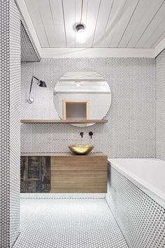 The residents of this maisonette, located in Prague's Vinohrady district, were a young couple returning to the Czech capital after living in London for several years. Stepanova took cues from London's industrial character (with a healthy dash of minimalist design) in devising this remodel's striking aesthetic. In the first bathroom, seen here, a brass washbasin from Morocco is flanked by a Tolomeo Micro Parete lamp from Artemide.
