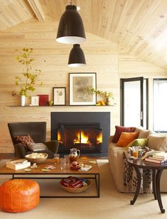 Light wood ceiling and walls; chocolate browns chair, metal pendant lamps, black framed glass door/fireplace