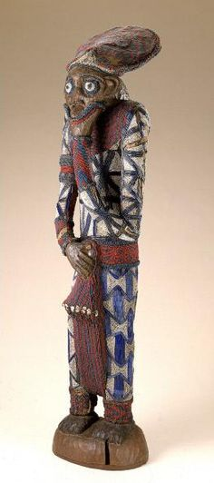 Africa | Male figure. Bamum peoples.  Cameroon, Famban | Wood, brass, cloth, glass beads, cowrie shells | This life-size male figure from the kingdom of Bamum in Cameroon is a visually compelling example of the splendid beaded sculptures Bamum artists created for the royal court in the 19th and early 20th centuries.