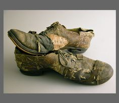 """Pranges Shoes  Extreme mends to leather and sole, heavily stitched & nailed together   in patchwork of canvas and rubber.  Midwest United States, ca 1st half of the 20th century  Height: 3-1/2"""", Width: 12-1/4"""", Depth: 4-1/2""""  Mr. Pranges was a wealthy business man from Milwaukee who refused to give   up his shoes so, """"wear and repair"""" he did until his death did they part."""