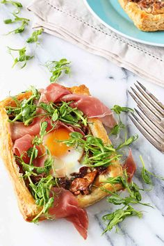 Flaky puff pastry cradles delicious butter sautéed chanterelles, a flowing golden egg yolk, salty prosciutto and lemony pea shoots in the perfect handheld tart.