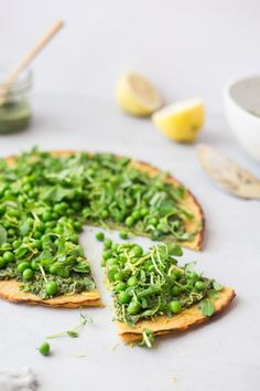 chickpea flatbread topped with a spicy mustard greens pesto, pea shoots, sweet peas and lemon zest #vegan #glutenfree