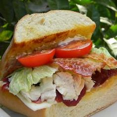 "Turkey Sandwiches with Cranberry Sauce | ""Layer French bread wedges with sliced turkey, bacon, Provolone cheese, tomatoes, and jellied cranberry sauce to make a hearty broiled sandwich with the taste of Thanksgiving."""