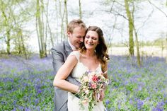 bride and groom laughing in a field of bluebells at pitt hall barn spring wedding