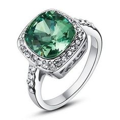 Round cut green crystal stone that is surrounded by smaller round cut crystals