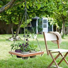 Pots de fleurs incrustés dans une planche de bois reliée à des cordelettes comme une balançoire