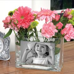 This elegant personalized glass photo vase makes an ideal gift for either a man or a woman. Create a one of a kind gift by inserting a favorite photo and having a special sentiment engraved at the top of the vase. The personalized vase can hold either real or dried flowers, or even office supplies, making it a great birthday gift, thank you gift or holiday present for friends, family and coworkers! It also makes for a truly stunning, inexpensive centerpiece to a wedding reception table!
