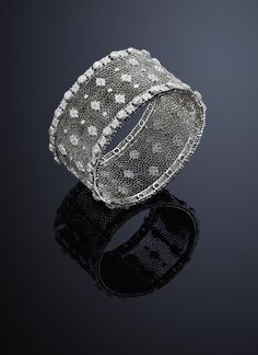 A diamond bangle, by Gianmaria Buccellati The pierced openwork 'honeycomb' centre regularly set with lozenge-shaped pavé-set diamond motif and diamond accents flanked by circular-cut diamond and pavé-set diamond clusters, to rigato engraving to the edges, inner diameter 5.4 cm, total diamond weight 9.44 carats, signed 'Buccellati'.
