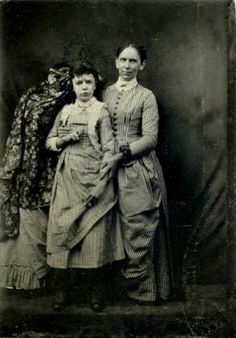 A partially covered person is to the dead girl's left and is helping to hold her upright for the photo (same child as in the wheelchair photo here).  ca. 1865, memento mori