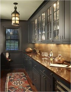 Copper counter tops and dark grey cabinets. Love the light fixture with it and the glass fronts for the cabinet doors too