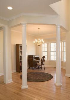 Round wood columns separating a main entrance from the for Columns in houses interior