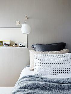conjunto de roupa de cama em tons neutros e luminária para leitura