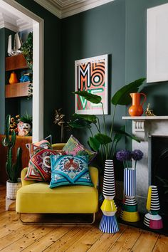 Colour crushing in this vibrant living room. The dark walls are given huge pops of colour with colourful cushions, maximalist vases and bold accessories like this bright orange jug on the mantlepiece. Colourful Living Room, Living Room Colors, Home Living Room, Living Room Designs, Jungle Living Room Decor, Bright Living Room Decor, Home Interior, Interior Design, Design Interiors