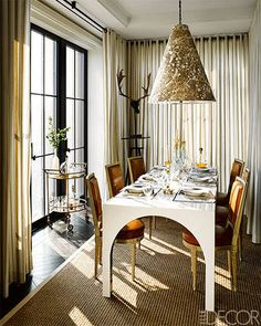 Napoleon III–style chairs from the 1890s surround a custom dining table; the lamp is custom made, the barware is from Arteriors, the flatware is by Christofle, and the sisal rug is by Stark.