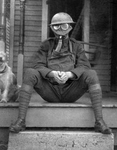 An American soldier wears his gas mask after World War I sitting on the front stoop of his house.
