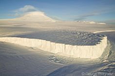 Photograph by George Steinmetz @geosteinmetz/@thephotosociety Barne Glacier where it meets the sea ice of McMurdo sound on it's descent from Mt. Erebus. Here Erebus is seen with an unusual double ring of clouds surrounding its summit. To see more photographs from Antarctica visit @geosteinmetz by natgeo