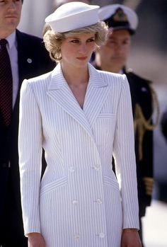 Striped Coat Dress by Catherine Walker: This is a fierce look on the Princess. A very becoming hat by Kangol tops this double-breasted pinstripe coat dress by one of her favorite designers. Diana wore this at a naval base during the 1985 Royal Tour of Italy.