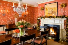A vibrant coral dining room decorated for Christmas.