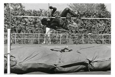 Black and white photo of an unidentified high jumper clearing the bar at Hayward Field circa 1970. ©University of Oregon Libraries - Special Collections and University Archives