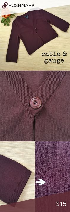 Cable & Gauge 3/4 Length Sleeve Cropped Cardigan Get into the autumn spirit with this beautiful maroon colored cropped cardigan by Cable & Gauge! The 3/4 length sleeves of this cardigan make it perfect for the cooler temperatures. The cardigan is held shut by one large maroon button. There is one small snag on the front left  side towards the bottom (see second pic in pic 3). Other than that, the top is in very nice condition. The cardigan is made of 62% viscose and 38% nylon. It is a size…