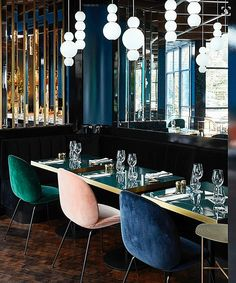 Velvet chairs in pink green and blue and art deco style lighting and mirrors