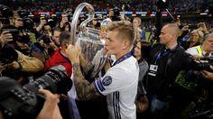 Kroos küsst von Fotografen umringt den Champions-League-Pott