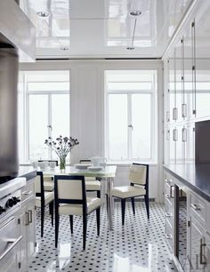 In a New York kitchen, 1930s chairs by Dominique upholstered in patent leather surround a custom-made glass-top table by the home's decorator, Delphine Krakoff.Pin it.
