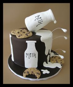 Mmmm....nothing is better than Spilt Milk and Cookies! Cake is Vanilla Bean Cake with cookies and cream filling and covered in chocolate fondant. Milk bottle on top is made out of rice cereal treats and covered in fondant. I used a dowel to make the bottle stand on it's side and small pieces of fondant on wrapped wires to make droplets. Cookies are also made out of fondant and mini chocolate chips and texturized with an actual chips ahoy cookie. TFL