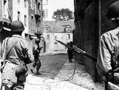 American soldiers on patrol in a French town, 1944. Notice the soldier with a M1919 Browning machine gun.
