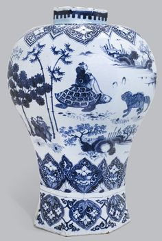 A large Dutch Delft blue and white vase, late seventeenth century of inverted baluster form, painted in manganese and blue with a procession of figures and mythical Chinese animals through a Transitional-style mountainous landscape, within elaborate floral and masked lappet borders