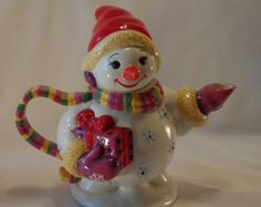 Christmas snowman (snowlady) teapot ... one arm holding present with bright red bow and the other outstretched to form spout, ceramic