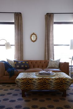 A tufted leather sofa from the Cobble Hill collection at ABC Carpet & Home is accented by Etsy throw pillows and custom draperies.