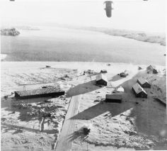 A Messerschmitt Bf 109 attempts to take off from the airfield at Herdla, Norway, during a successful low-level attack by 13 Bristol Blenheim Mark IVs of No. 114 Squadron RAF, in support of the Combined Operations raid on Vaagso. Photograph was taken with a rear-facing camera from one of the attacking aircraft, 27 Dec 1941.
