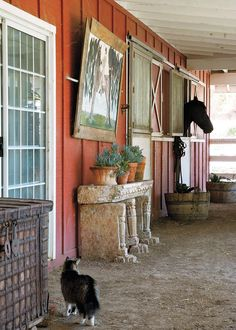 The stable has two horse stalls and a tack room. Inside, walls display show-ribbons and family photographs.