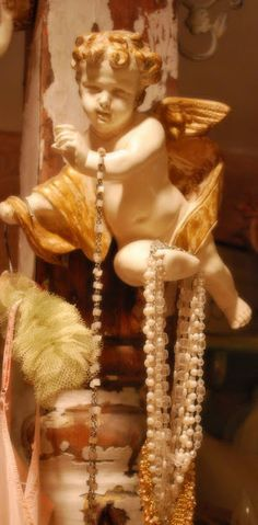 love.... This cherub holds a necklace and rosary beads. It hangs on a vintage, chippy, white architectural piece.