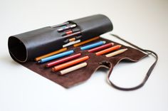 Expresso 27 Upcycled Leather Roll Up Pencil Case. Just find a good piece of scrap leather, xacto the holes for the pencils and attach a strap. should be super easy to diy